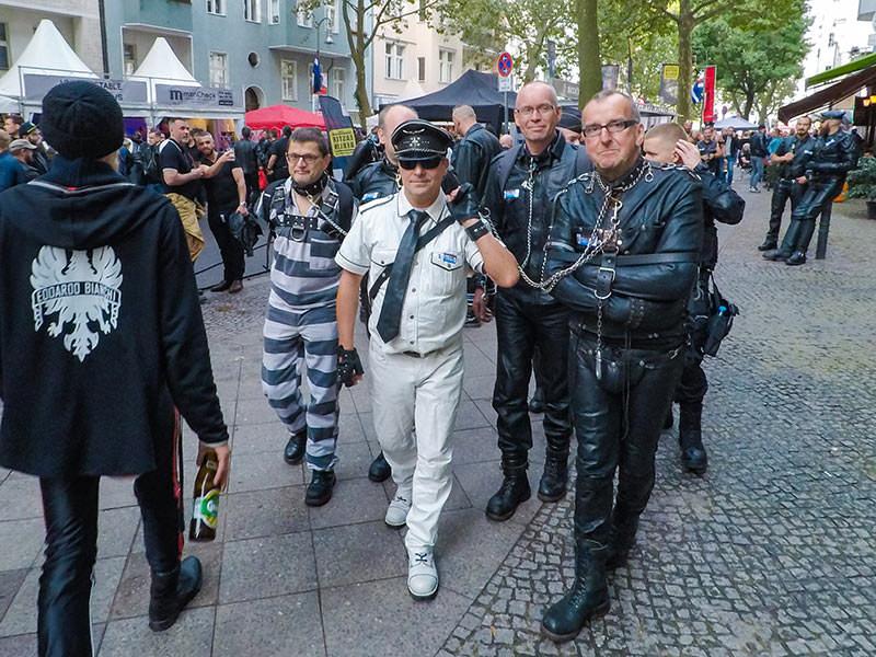 A man dressed in uniform is leading prisoners-looking men in chains at Folsom Europe Street Fair, the biggest European gay fetish event, in Berlin, Germany, photo by Ivan Kralj