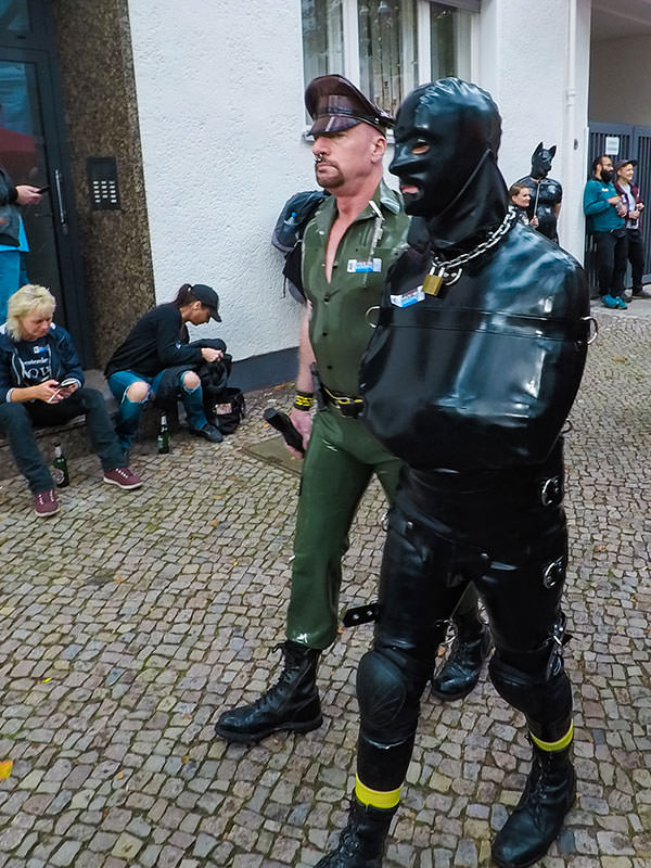 Man constrained in latex being escorted by a military-looking official at Folsom Europe Street Fair, the biggest European gay fetish event, in Berlin, Germany, photo by Ivan Kralj
