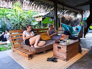 Guests resting on the sofas and hammocks on the terrace of Sae Sae, one of the best hostels of Java, in Yogyakarta, Indonesia, photo by Ivan Kralj