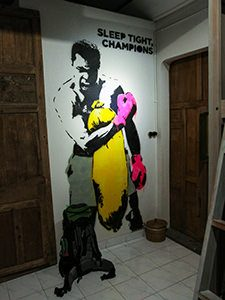 "Mural of boxer Mohammad Ali with a text saying ""Sleep tight, champions"" in the dorm of Sae Sae, one of the best hostels of Java, in Yogyakarta, Indonesia, photo by Ivan Kralj"