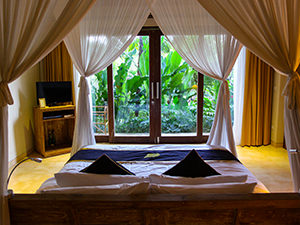 Bed with a view of a green terrace in Sankara Ubud Resort, one of the answers to where to stay in Bali, Indonesia, photo by Ivan Kralj