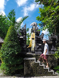 Blogger Ivan Kralj in traditional Balinese costume climbing to the little shrine in front of Sankara Ubud Resort, one of the answers to where to stay in Bali, Indonesia, photo by Ivan Kralj