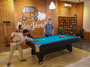 Guests playing billiard in the lobby of Wonderloft, one of the best hostels of Java, in Jakarta, Indonesia, photo by Ivan Kralj