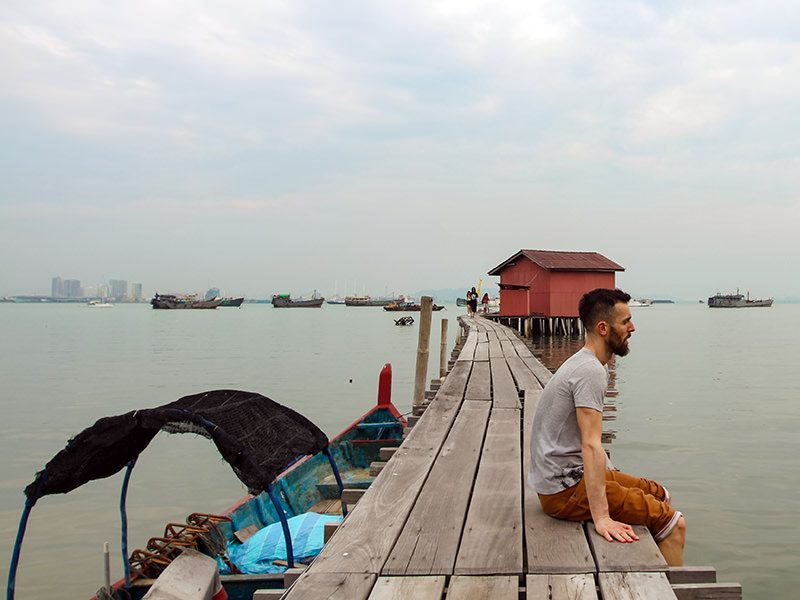 Pipeaway blogger Ivan Kralj sitting on one of the jetties in Georgetown, Penang Island, Malaysia, boats lining up on the horizon, photo by Weile Ng