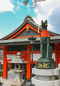 Fox statue with red napkin in front of the Fushimi Inari Taisha temple in Kyoto, Japan, photo by Ivan Kralj