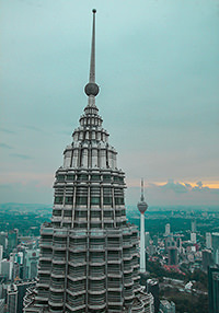 One of the Petronas twin towers and KL Tower in the background with an urban landscape of Kuala Lumpur, Malaysia, photo by Ivan Kralj