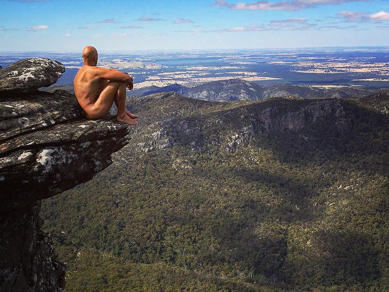 Erik, the Australian naked hiker, sitting on the edge of the cliff, with a beautiful mountain forest view