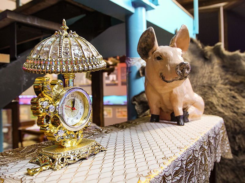 Golden clock and porcelain pig figurine as part of kitchy interior design display at Romanian Kitsch Museum in Bucharest, Romania, photo by Ivan Kralj
