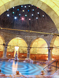 Octagonal pool in the main hall of Rudas Baths, covered with a hemispheric dome with colorful little glass windows