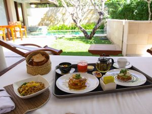 Bali honeymoon breakfast - a variety of food served at the daybed in the privacy of one of the villa pavilions, with swimming pool in the background, in the Balé resort, in Nusa Dua, in Bali, Indonesia, photo by Ivan Kralj