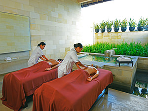 A couple receiving a massage by two masseuses at the spa in the Bale resort, at Bali honeymoon, in Nusa Dua, Bali, Indonesia