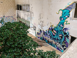 An atrium in the abandoned Hotel Belvedere Dubrovnik, Croatia, with a growing tree and large street art mural on the wall, photo by Ivan Kralj