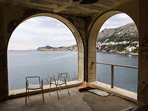 Two chairs on a terrace in the abandoned Hotel Belvedere Dubrovnik, Croatia, with a view of the seaside and the Old Town, photo by Ivan Kralj