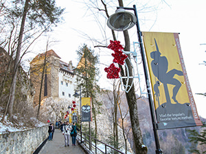 Pathway towards the Bran Castle, also known as Dracula Castle, with poster of impaled men silhouettes, in Transylvania, Romania, photo by Ivan Kralj