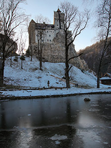 Bran Castle, also known as Dracula Castle, on the snow-covered hill above the frozen pond in the English garden, in Transylvania, Romania, photo by Ivan Kralj
