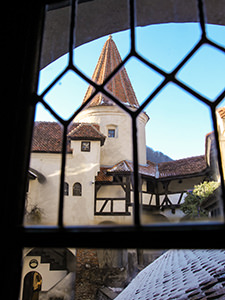 Bran Castle (also known as Dracula Castle) red-tile covered tower shot through the grid window, photo by Ivan Kralj