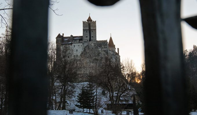 Bran Castle, also known as Dracula Castle, on a snow-covered hill in Transylvania, Romania, shot during sunset through the hole in the fence, photo by Ivan Kralj
