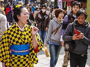 Asian lady in yellow-and-black checkered kimono licking a penis-shaped lollipop on the street of Kawaski, Japan, during Kanamara Matsuri festival, photo by Ivan Kralj