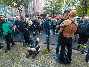 Two men kissing and one man playing a puppy next to his cigar-smoking owner on the street in Berlin, Germany, during Folsom Europe gay fetish festival, photo by Ivan Kralj