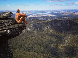 Australian naked hiker Erik sitting on the edge of the cliff in the mountains