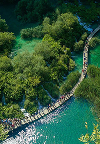 Visitors of Plitvice Lakes national park in Croatia walking over a wooden pathway over green lakes, from bird's eye perspective, photo by Ivan Kralj