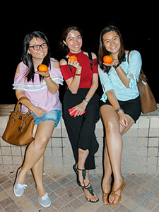 Three young Malaysian women posing with mandarin oranges on which they wrote their names, wishes and phone numbers before throwing them into the sea, hoping that Mr. Right would pick them up on Chap Goh Mei, Chinese Valentine's Day, in George Town, Penang, Malaysia, photo by Ivan Kralj