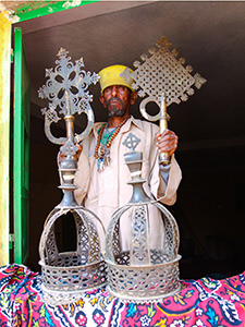 The monk at Abba Pentalewon monastery in Askum, Ethiopia, displaying ceremonial crosses and crowns of the King Kaleb and his son Gebre Meskel, photo by Ivan Kralj