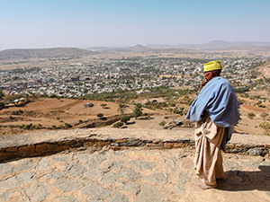 Monk of hilltop Abba Pentalewon monastery standing in front of the panorama of Aksum, Ethiopia, photo by Ivan Kralj