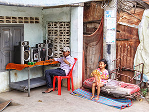Cambodian boy sitting next to the sound system installed on the table in front of his house, while his sister plays with a doll, in Battambang, during the Khmer New Year, photo by Ivan Kralj