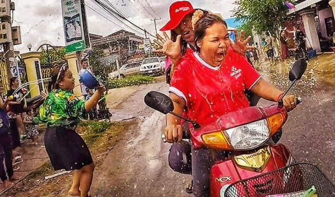 Women on motorbike getting splashed with water during Songkran water festival for Khmer New Year in Battambang, Cambodia, photo by Ivan Kralj