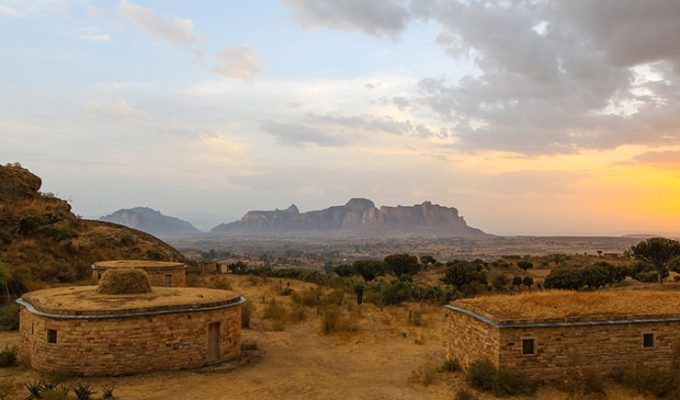 Bungalows of Gheralta Lodge at sunset, with a view of misty Gheralta Mountains in distance, Tigray Region, Ethiopia, photo by Ivan Kralj