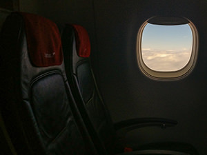 Empty seats in the plane with clouds viewable through the window - jet lag might be affecting travel fogginess, photo by Ivan Kralj