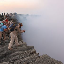 Visitors looking into and taking photographs at the edge of the smoke-filled crater at Erta Ale volcano in Danakil Depression, Ethiopia, the hottest place on Earth, photo by Ivan Kralj