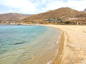 The sandy Vagia Beach on Serifos island, with Coco-Mat Eco Residences in the background, one of the best beachfront hotels in Cyclades Islands