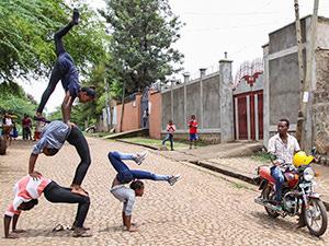 Girl performers from Arba Minch Circus build a human pyramid on the street while a confused motorbike rider passes by, Ethiopia, photo by Ivan Kralj