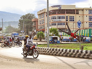 Acrobat from Arba Minch Circus performing a 'human flag' figure on the traffic sign at the roundabout in Arba Minch, Ethiopia, while the motorbikes and bajajs participate in traffic, photo by Ivan Kralj