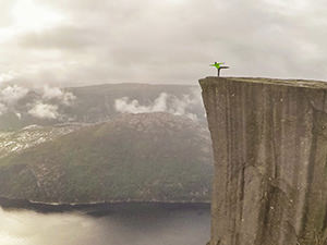 Man standing on one foot on the edge of Preikestolen or Pulpit Rock, square-shaped mountain plateau and the famous hiking destination at Lysefjord, Norway, photo by Ivan Kralj