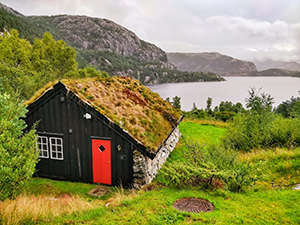 Black-walled house with red door and grass-covered roof at the shore of Revsvatnet lake, the starting point of Preikestolen / Pulpit Rock hike in Norway, photo by Ivan Kralj