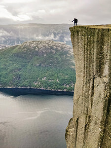 Man using a selfie stick to take photographs beyond the edge of Preikestolen or Pulpit Rock, square-shaped mountain plateau and the famous hiking destination at Lysefjord, Norway, photo by Ivan Kralj