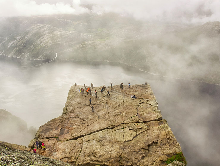 Preikestolen or Pulpit Rock, square-shaped mountain plateau and the famous hiking destination at Lysefjord, Norway, photographed from above, with people observing the surrounding from its edge, and clouds forming above the fjord, photo by Ivan Kralj