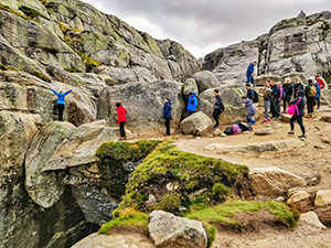 Back side view of the Kjeragbolten - people queuing up to take photos on the famous Kjerag boulder in Norway, photo by Ivan Kralj
