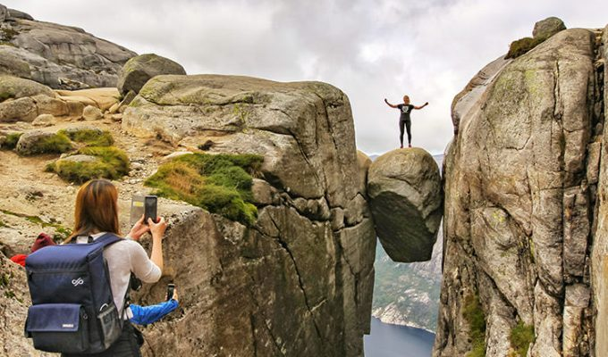 Girl photographing her friend standing on Kjeragbolten, a famous boulder on Kjerag Mountain, Norway, photo by Ivan Kralj