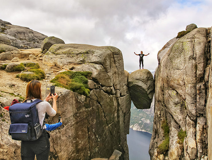 Girl photographing her friend standing on Kjeragbolten, a famous boulder on Kjerag Mountain, Norway, photo by Ivan Kralj