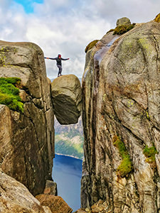A girl using someone's assisting hand to step on Kjeragbolten, a famous boulder on Kjerag Mountain, Norway, photo by Ivan Kralj