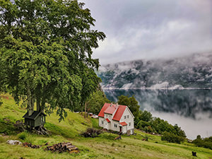 Treehouse and Director's Villa with foggy mountain and calm waters of Lysefjord in the background, at Flørli 4444, in Norway, photo by Ivan Kralj