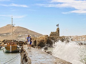 Tourists crossing the walkway to Venetian Castle in Naoussa, trying to avoid the splashes of the sea waves, photo by Ivan Kralj
