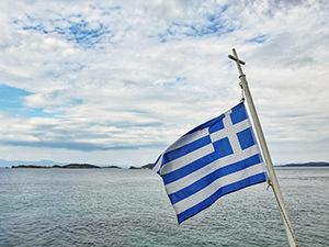 Greek flag on the pole with a cross, on the ferry to Mount Athos, the peninsula of monasteries in Greece, photo by Ivan Kralj