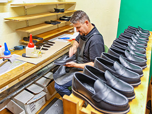Worker in the workshop of Aurland Shoe Factory making Aurland shoes, in Norway, photo by Ivan Kralj