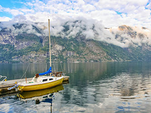 Boat in Aurlandsfjord surrounded by cloudy mountains, at Aurlandsvangen, Aurland, Norway, photo by Ivan Kralj