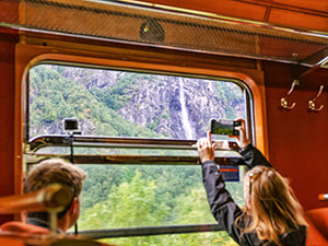 Tourists in the Flam Railway train photographing the waterfall through the window, one of the things to do in Aurland, Norway, photo by Ivan Kralj